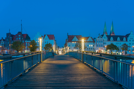 Historical cityscape with pedestrian bridge on the river Trave in Lubeck at the Baltic Sea