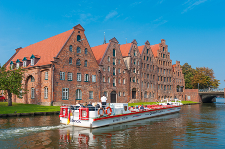 Salt storage, historic salt storage warehouses and excursion ship on the River Trave in Lubeck at the Baltic Sea Editorial
