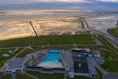 Drone view, Landscape with the Wadden Sea and the Watt'n Bad open-air swimming pool. Dorum-Neufeld in Lower Saxony in Germany