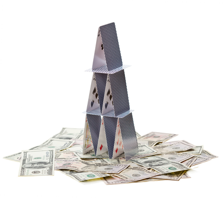economic depression: House of cards and money isolated on white background; symbol of financial crisis Stock Photo