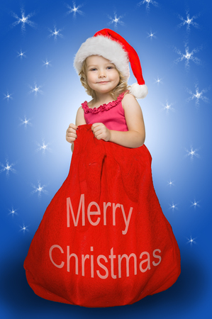 clause: Little cute girl dressed in santa clause costume in big Christmas bag