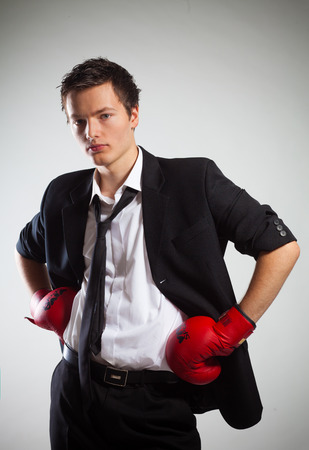 conflictos sociales: El hombre de negocios con guantes de boxeo, sobre fondo gris Foto de archivo