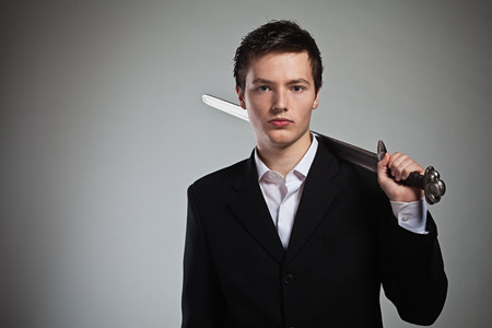 Businessman with sword ready for war