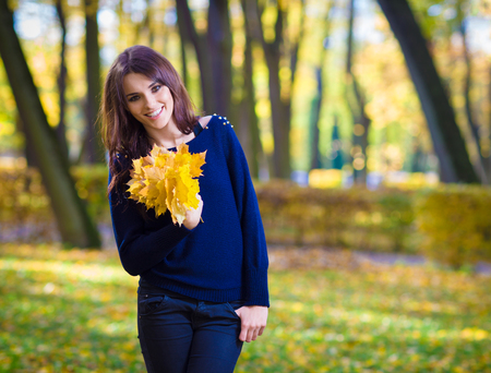 eastern european ethnicity: Portrait of smiling, young woman, holding a bunch of autumn maple leaves. Stock Photo