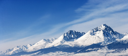 mountain valley: Snow capped summit of Tatry high under clear blue panoramic skies.