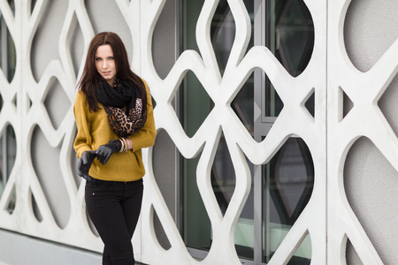leather gloves: Young Woman posing near the modern building
