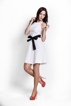Glamour girl in dress on white Imagens