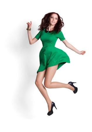 salto de longitud: Mujer atractiva joven que salta en el aire. Aislado en blanco