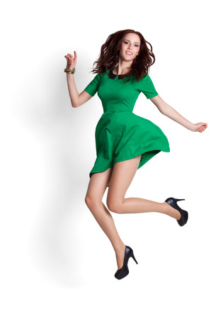 long jump: Young attractive woman jumping in the air. Isolated on white