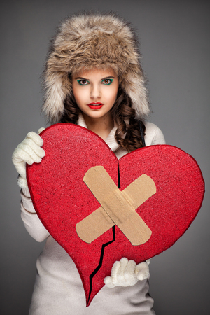 broken love: pretty woman squeezing Valentine heart in her arms against gray background