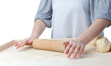 roll out: hands roll out dough on kitchen countertop Stock Photo