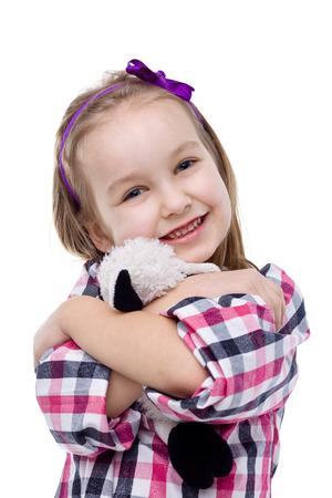 loved: Little girl hugging her loved Teddy bear.