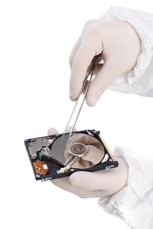 disco duro: disco duro y pinzas en la mano aisladas sobre fondo blanco