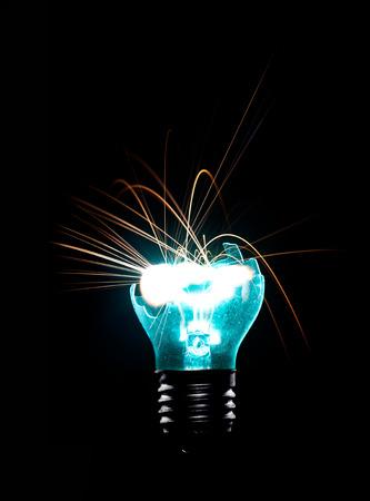 idea generation: Broken Light bulb burning in dark Stock Photo