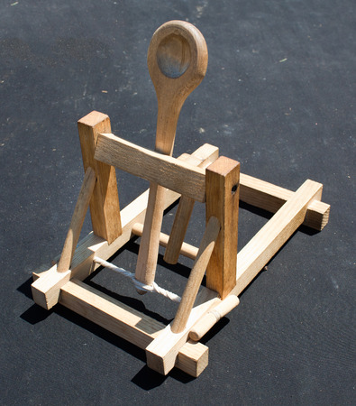siege: Wooden catapult toy on dark background
