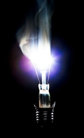 the franklin: Broken Light bulb burning in dark Stock Photo