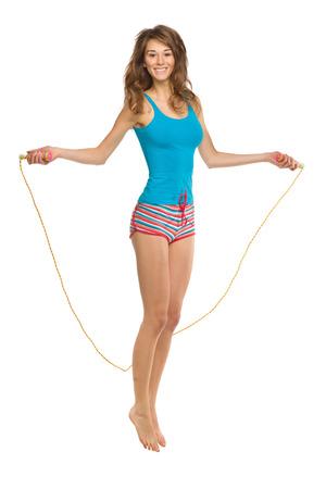 vue sur toute la longueur d'une jolie femme dans la corde à sauter de l'air; Isolé sur blanc