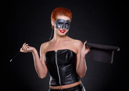 beautiful redhead: Beautiful redhead Female magician in dark.