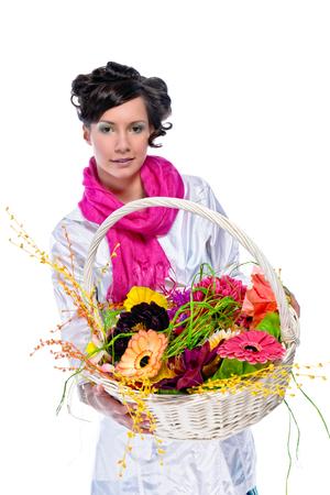 花でいっぱいバスケットを持つ美しい若い女性