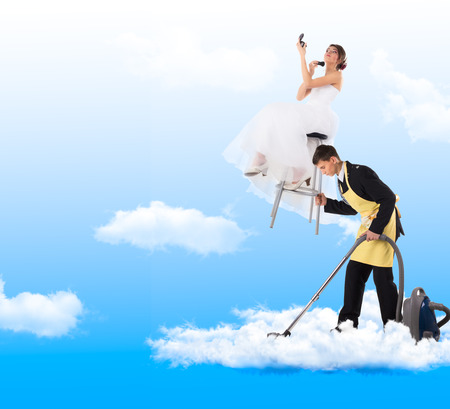 cleaning equipment: Woman sitting on the stool holding a mirror, man hoovering in clouds.