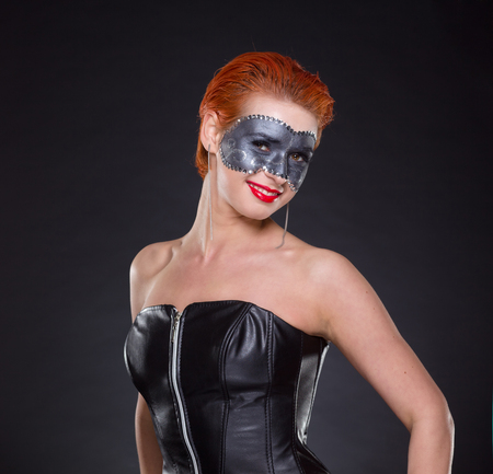 Beautiful young woman posing as pinup girl in black leather corset. Professional hair and makeup.