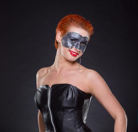 Bella giovane donna in posa come ragazza pinup in corsetto di cuoio nero. Capelli e trucco professionali.
