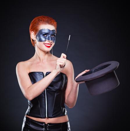 abracadabra: Beautiful redhead Female magician in dark.