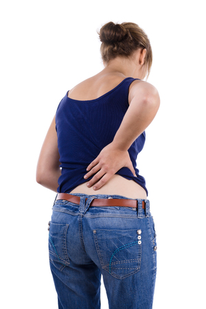 dolor espalda: Mujer en camisa azul y pantalones vaqueros sosteniendo baja de la espalda en el dolor
