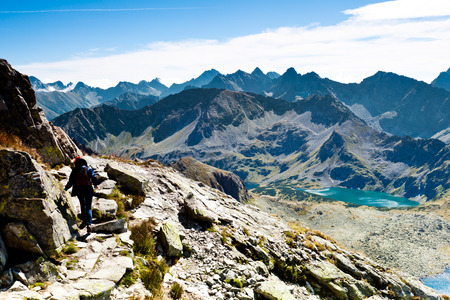 getting away from it all: Woman Hiking Up Steep Hill with Backpacks and Rocky Mountain View Stock Photo