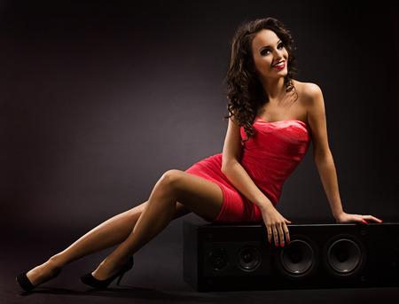 mujer desnuda sentada: Chica en vestido rojo, sentado en la etapa altavoz grande de audio.