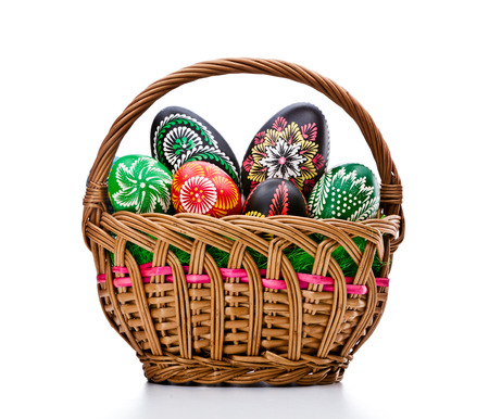 eastertime: Woven basket full of eggs. Isolated on a white background. Stock Photo