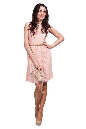 若いかわいい女性がベージュのドレスでポーズ