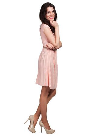 Schattige jonge vrouw die zich in beige jurk