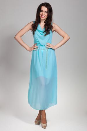 Schattige jonge vrouw poseren in blauwe jurk