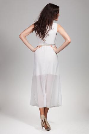 Schattige jonge vrouw poseren in witte jurk Stockfoto