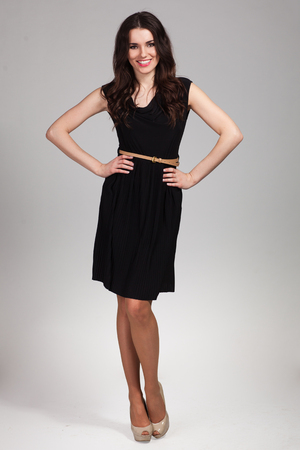 Young cute woman posing in black dress