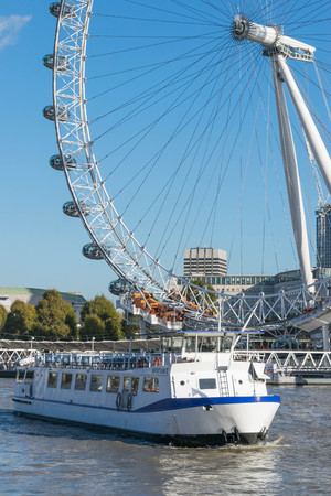 LONDON, UK - October 17th, 2017: Close up of the London Eye in London, England with tourism holding capsule in view and thames river crusing ships in the foreground. Editorial