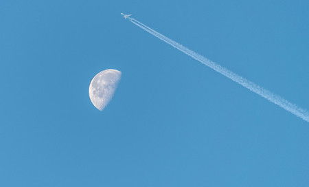 Waning Gibbous Moon near last quarter, daytime shot with an aeroplane over the moon.