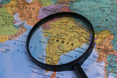 Map of India through magnifying glass on a world map.