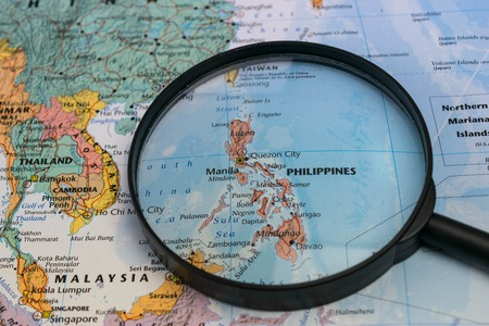 Map of the Philippines through magnifying glass on a world map.