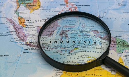 Map of Indonesia through magnifying glass on a world map.