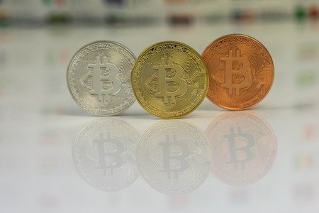 Close up of Bitcoins, gold bitcoin, silver bitcoin and bronze bitcoin with blurred background of world flags. reflection of the bitcoins visible. Stock Photo