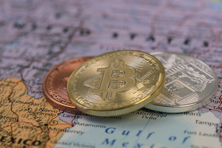Golden Bitcoin Coin close up together with silver bitcoin and bronze bitcoin with blurred background of United States map.