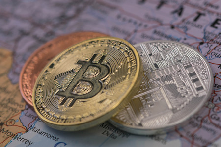 Golden Bitcoin Coin close up together with silver bitcoin and bronze bitcoin with blurred background of United States map