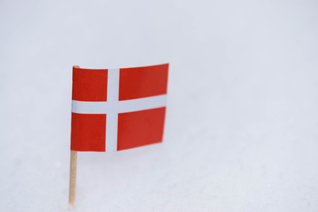 Denmark flag made from paper with brown toothpick on white snow background. 스톡 콘텐츠