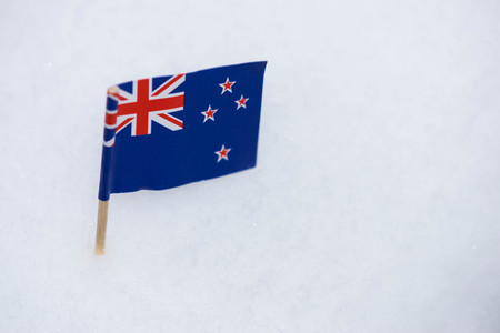 Australia flag made from paper with brown toothpick on white snow background.