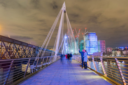 London, United Kingdom, February 17, 2018: long exposure of people walking and taking photos on Queens Golden Jubilee Footbridges near Charring Cross station