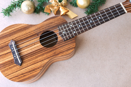 The ukulele on the wooden table with christmas golden decoration, ukulele is a gift from the christmas day
