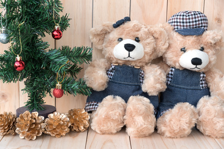 teddy bear love: two teddy bears with christmas tree on wood background, concept love