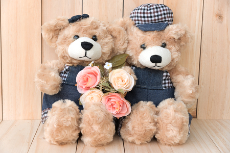 teddy bear love: two teddy bears with roses on wood background, love concept for valentines day, wedding and anniversary